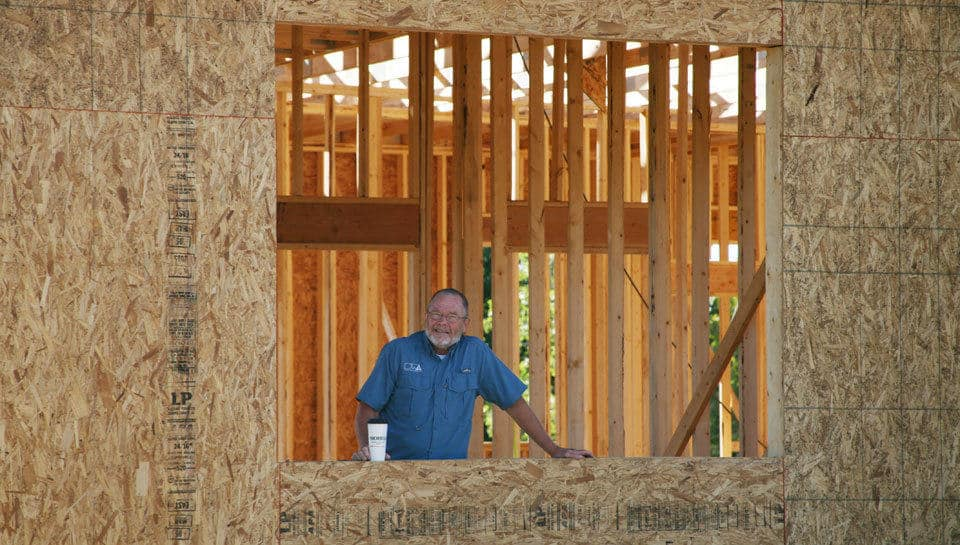 Architect Brad Wright stands in the window opening of what will be his new office at the home of PWArchitects on Colony Drive.