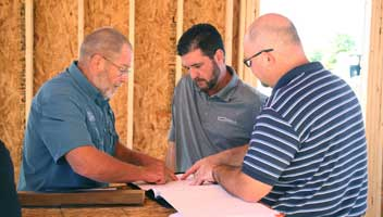 Brad Wright and Erik Miller goes over plans for the new office with contractor Jake Hunget of GBH Builders.