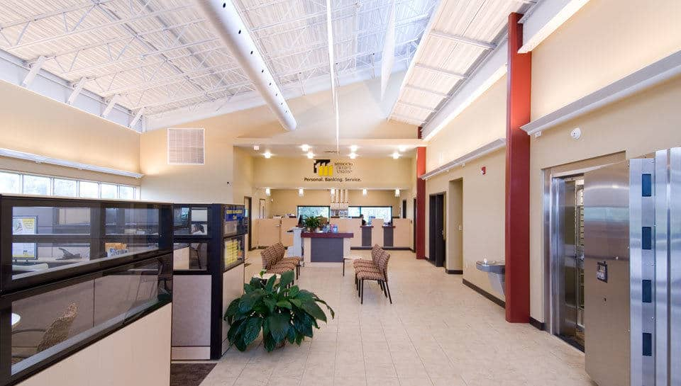 Light-colored materials, banners and a light shelf help to illuminate the interior of Missouri Credit Union in Columbia, Missouri.