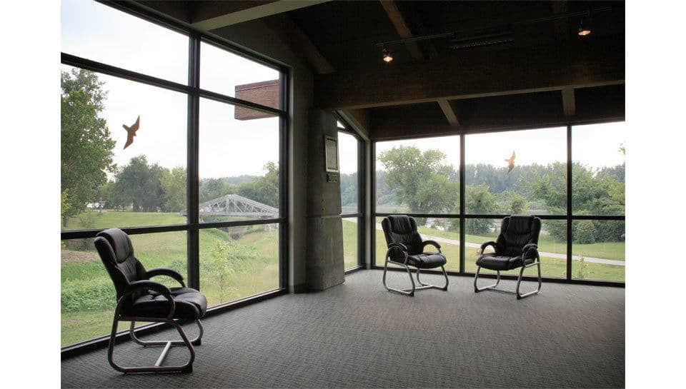 A bank of windows in the Remington Nature Center overlook Roy's Branch creek which outlets to the Missouri River nearby.