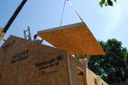 Laborers maneuver the SIPS of the Eco Schoolhouse roof into place.