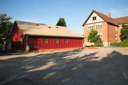 """The Eco School House is bounded on the north by a small existing parking lot, on the south and east by """"trailer classrooms,"""" and on the west by the existing school. A native landscape planted by a parents group replaced 1,000 square feet of asphalt."""